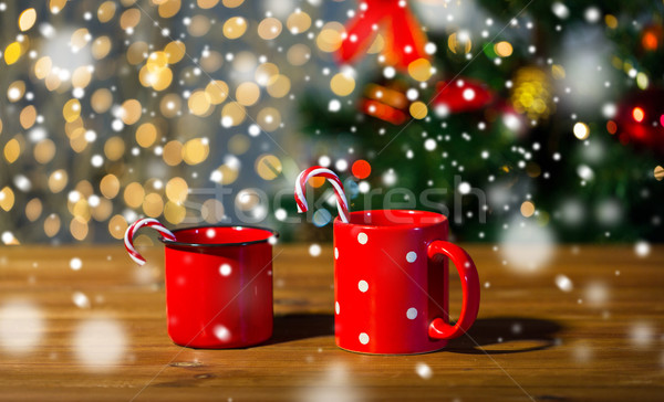 christmas candy canes and cups on wooden table Stock photo © dolgachov