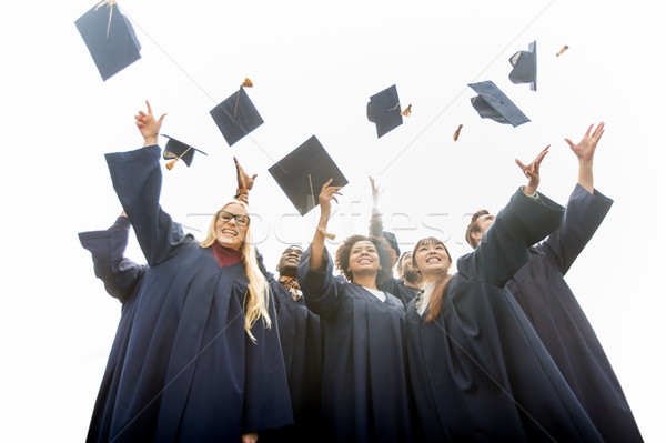 Stock photo: happy students throwing mortar boards up