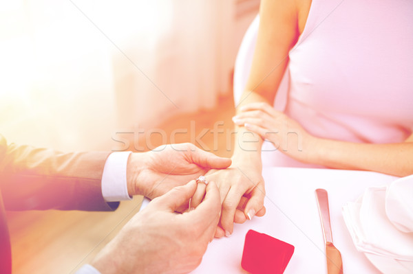 close up of man putting ring to his fiance finger Stock photo © dolgachov
