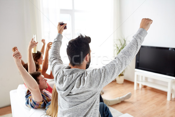 happy friends with beer watching tv at home Stock photo © dolgachov