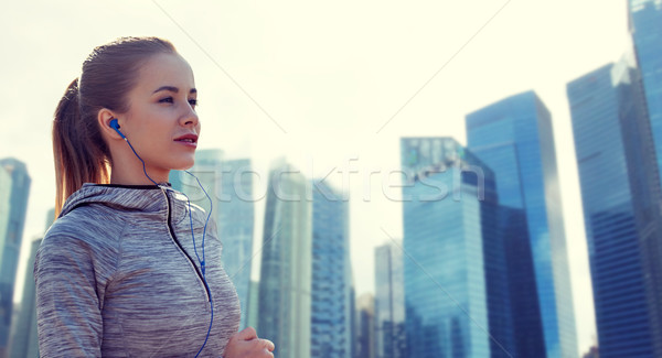 happy woman with earphones running in city Stock photo © dolgachov