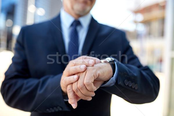 senior businessman with wristwatch on city street Stock photo © dolgachov