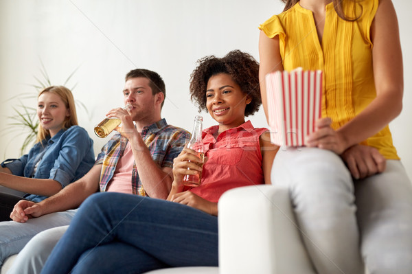 happy friends with popcorn watching tv at home Stock photo © dolgachov