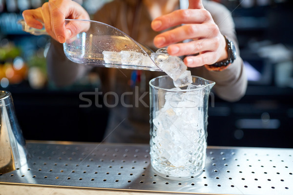 bartender pouring ice into glass jug at bar Stock photo © dolgachov