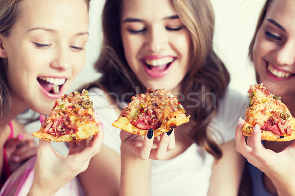 happy friends or teen girls eating pizza at home Stock photo © dolgachov