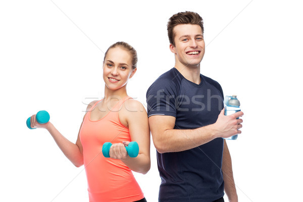 Stock photo: sportive man and woman with dumbbell and water