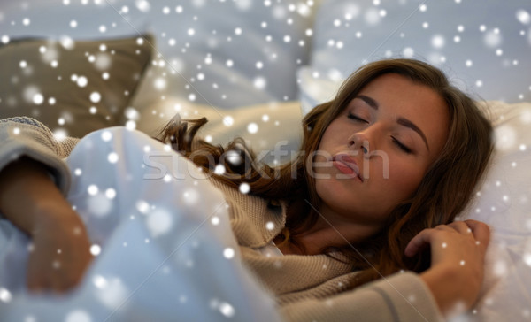 young woman sleeping in bed at home Stock photo © dolgachov