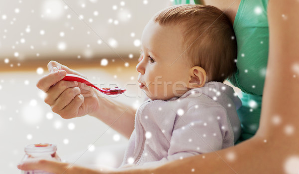 close up of mother with spoon feeding little baby Stock photo © dolgachov