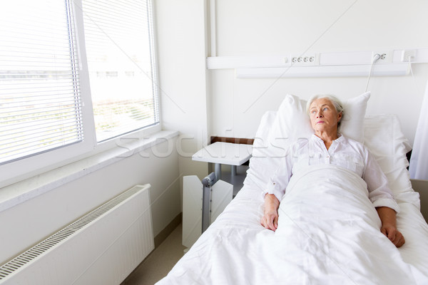 Triest senior vrouw bed ziekenhuis geneeskunde Stockfoto © dolgachov