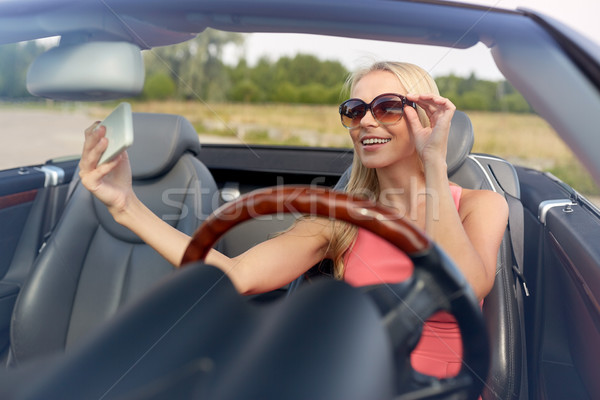 woman in convertible car taking selfie Stock photo © dolgachov