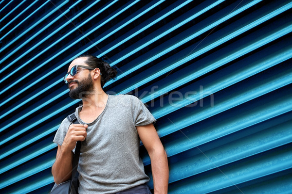 man in sunglasses with bag standing at street wall Stock photo © dolgachov