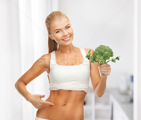 woman pointing at her abs and holding broccoli Stock photo © dolgachov