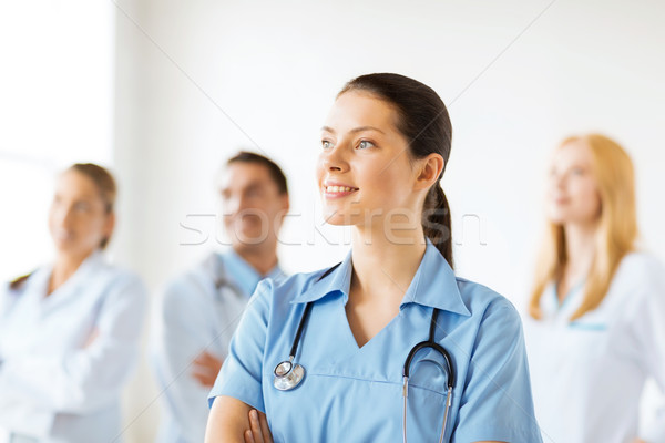 female doctor in front of medical group Stock photo © dolgachov