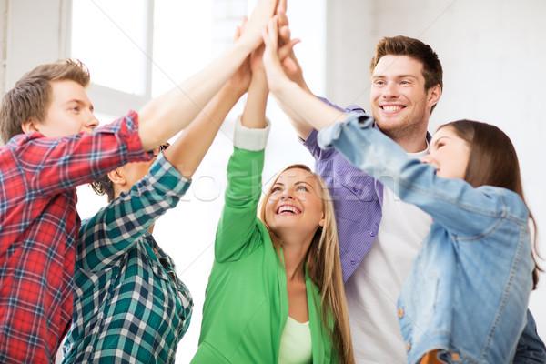 happy students giving high five at school Stock photo © dolgachov