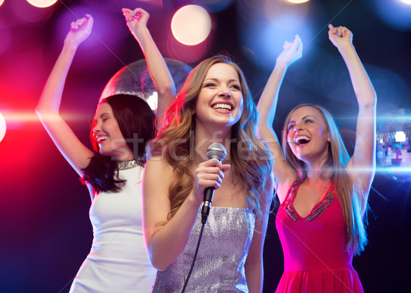 three smiling women dancing and singing karaoke Stock photo © dolgachov