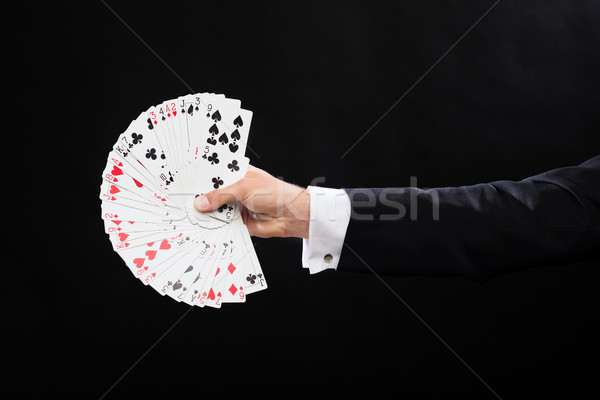 close up of magician hand holding playing cards Stock photo © dolgachov