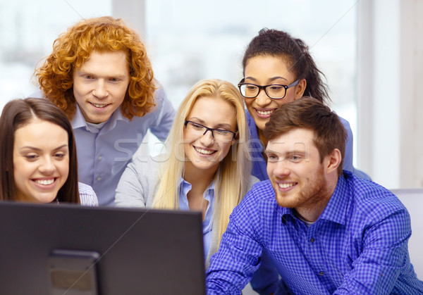 smiling business team looking at computer monitor Stock photo © dolgachov