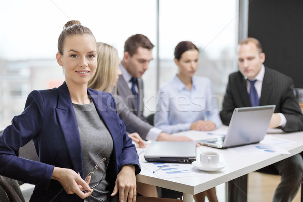businesswoman with glasses with team on the back Stock photo © dolgachov