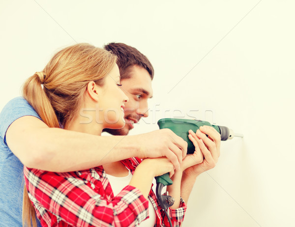 smiling couple drilling hole in wall at home Stock photo © dolgachov