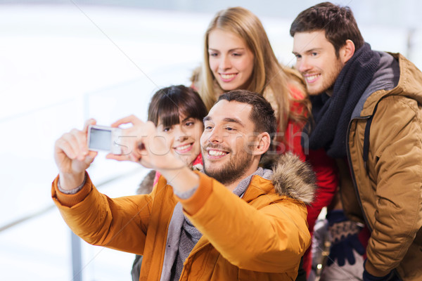 Stock photo: happy friends with camera on skating rink