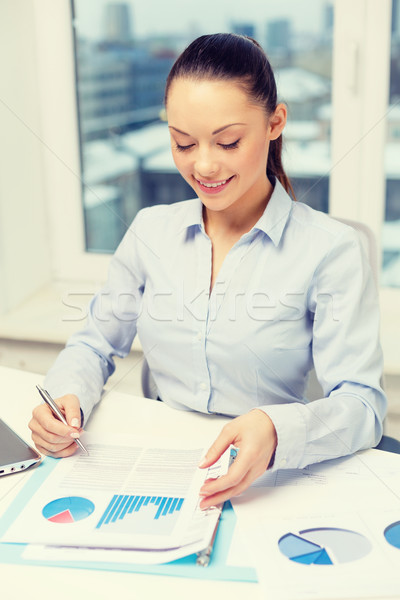 businesswoman with laptop and charts in office Stock photo © dolgachov