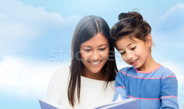 happy mother and daughter reading book Stock photo © dolgachov