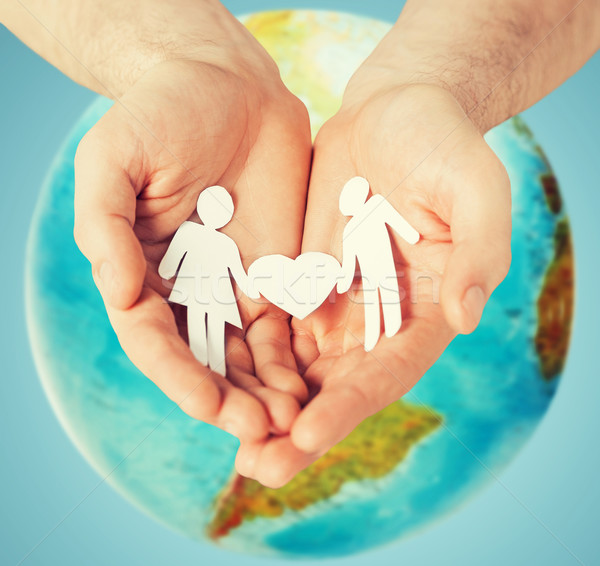 human hands holding paper couple over earth globe Stock photo © dolgachov