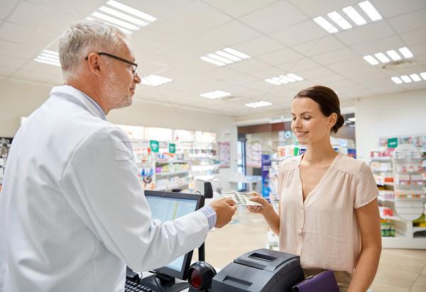 woman giving money to pharmacist at drugstore Stock photo © dolgachov