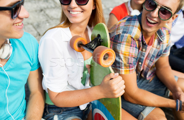 close up of happy friends with longboard on street Stock photo © dolgachov