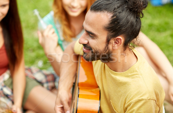 happy man with friends playing guitar at camping Stock photo © dolgachov