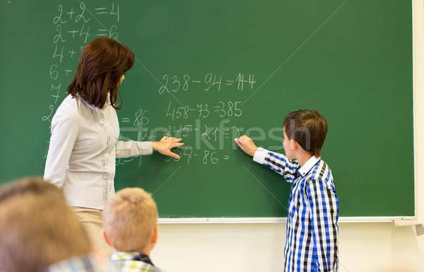 schoolboy with math teacher writing on chalk board Stock photo © dolgachov