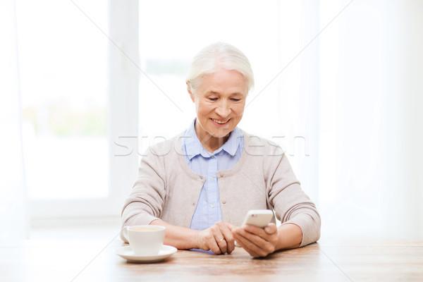 senior woman with smartphone texting at home Stock photo © dolgachov