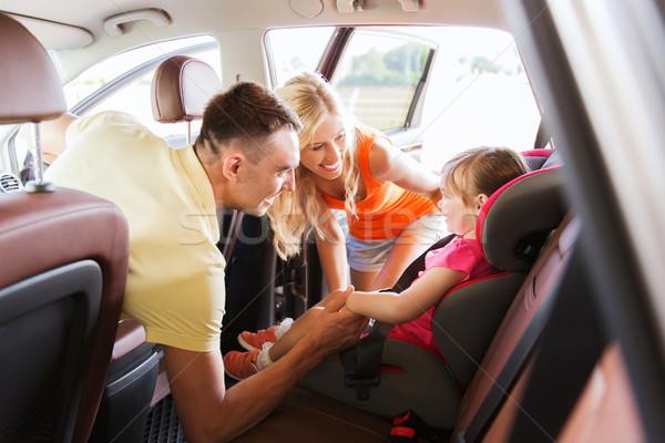 Stock photo: parents talking to little girl in baby car seat