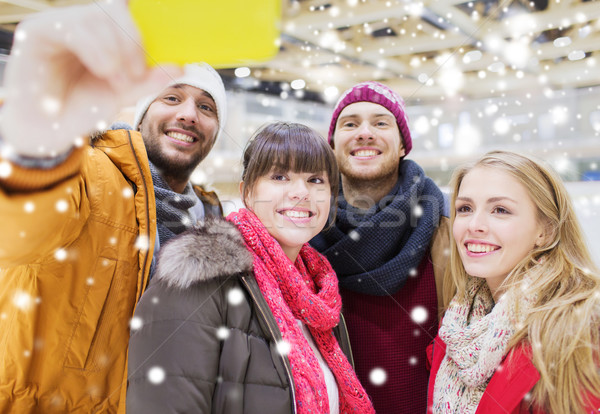 Stock photo: happy friends with smartphone on skating rink