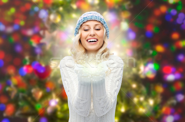 woman in winter hat holding fairy dust on palms  Stock photo © dolgachov