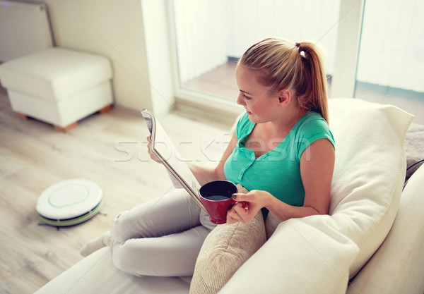 happy woman reading magazine with tea cup at home Stock photo © dolgachov