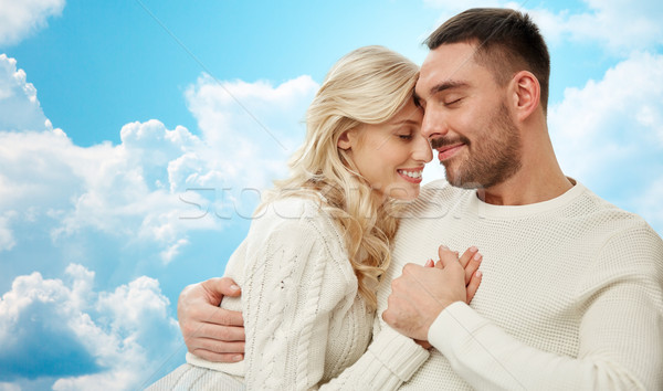 happy couple cuddling over blue sky and clouds Stock photo © dolgachov