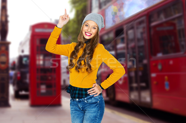 happy young woman or teen girl pointing finger up Stock photo © dolgachov
