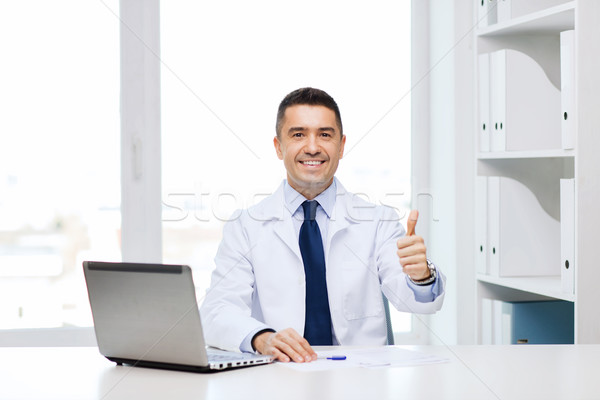 smiling doctor showing thumbs up in medical office Stock photo © dolgachov