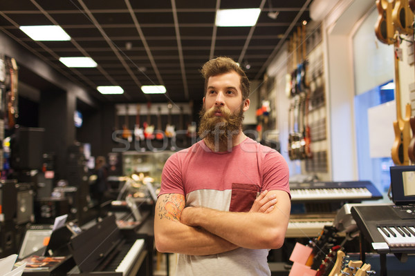 assistant or customer with beard at music store Stock photo © dolgachov
