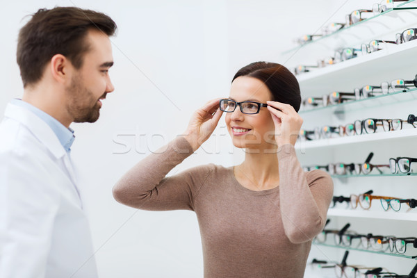 woman choosing glasses at optics store Stock photo © dolgachov