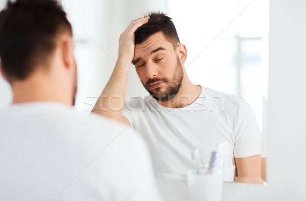 álmos fiatalember tükör fürdőszoba reggel ébredés Stock fotó © dolgachov