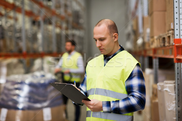man with clipboard in safety vest at warehouse Stock photo © dolgachov