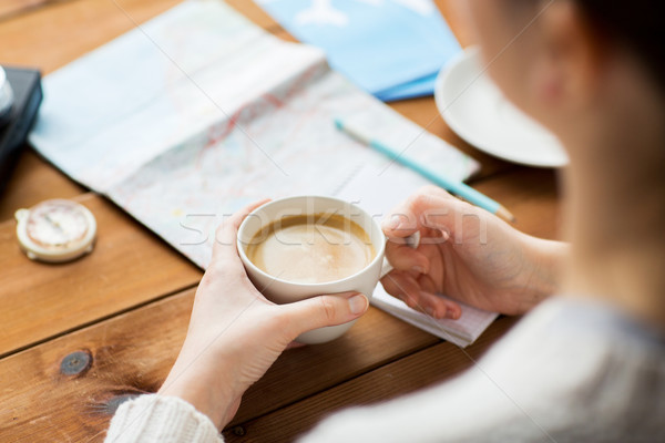 close up of hands with coffee cup and travel stuff Stock photo © dolgachov