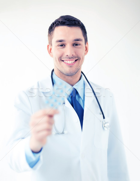 young male doctor with pack of pills Stock photo © dolgachov
