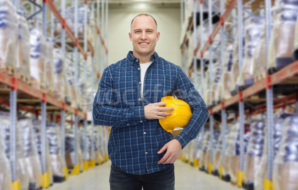 Stock photo: happy man with hardhat over warehouse