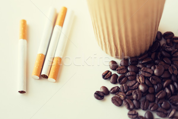 close up of cigarettes, coffee cup and beans Stock photo © dolgachov