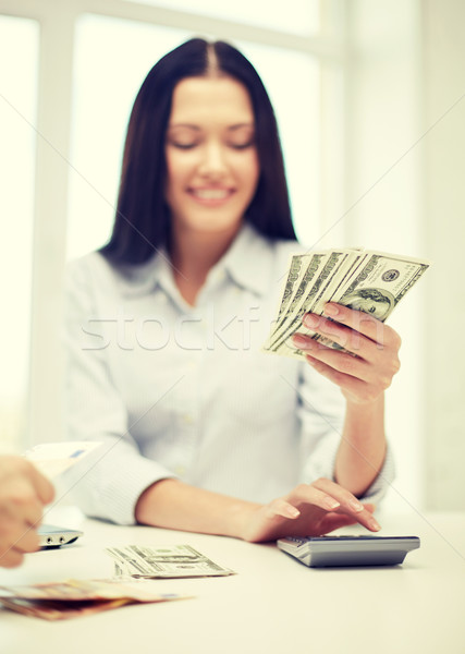 Stock photo: close up of woman counting money with calculator