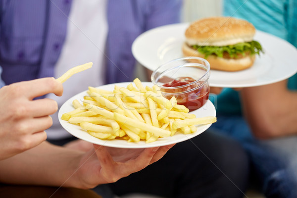 Stock photo: close up of male hands with fast food on plates