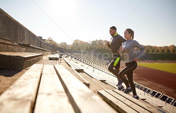 happy couple running upstairs on stadium Stock photo © dolgachov